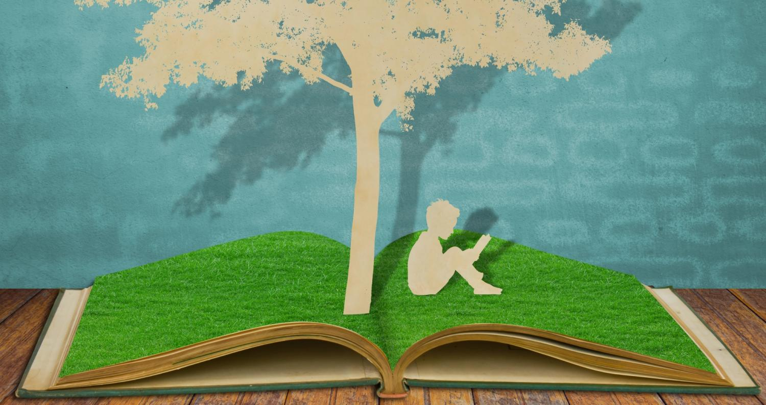 Child reading under a tree