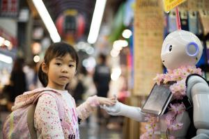 Child holding hands with a robot in Japan. Photo: Andy Kelly, Unsplash